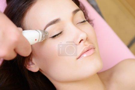 Photo pour Beau visage de jeune femme et traitement rajeuni, Dame se trouve sur un canapé dans un spa de beauté s'électrostimulation thérapie de levage - image libre de droit