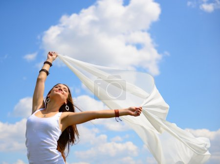Photo pour Joyeux jeune femme tenant écharpe blanche avec les bras ouverts exprimant la liberté, tir extérieur contre le ciel bleu - image libre de droit
