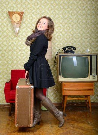 Photo pour Portrait d'art de la jeune femme tenant grosse valise dans la chambre avec le papier peint et l'intérieur avec tv, horloges, chaise et valise, stylisation rétro des années 60-70, tonique - image libre de droit