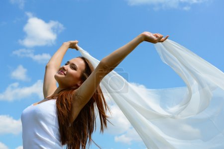 woman holding white scarf against sky