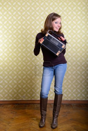Photo for Art portrait of young smiling ecstatic woman holding radio player in room with vintage wallpaper, retro stylization 60-70s, toned - Royalty Free Image