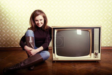 Smiling woman sitting near retro tv
