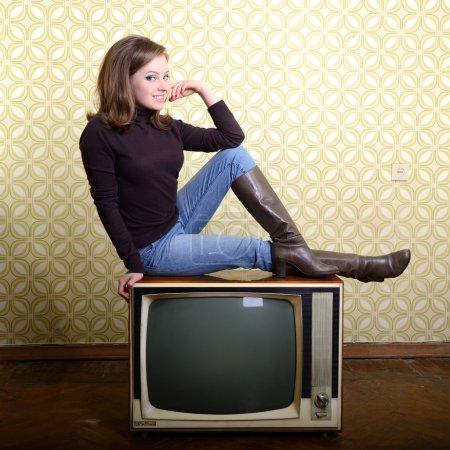 smiling woman sitting on retro tv