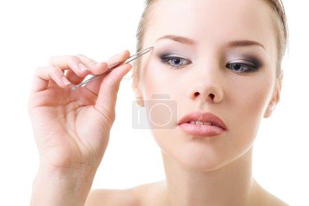 Photo pour Belle fille plumant les sourcils avec des pinces sur blanc - image libre de droit
