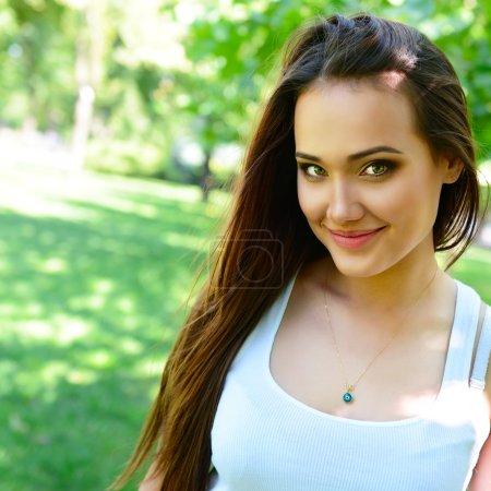 Photo pour Portrait de jeune belle femme aux longs cheveux bruns regardant la caméra, en plein air - image libre de droit