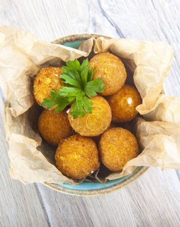 Photo for Appetizer spicy cheese balls in a plate on a wooden background top view - Royalty Free Image