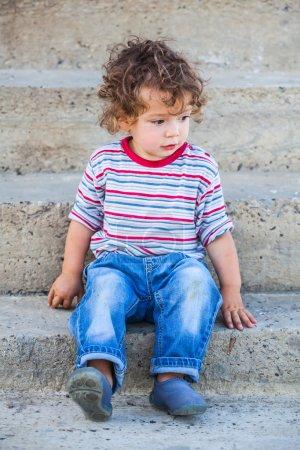 Photo pour Portrait de bébé garçon de 1 an assis sur l'escalier . - image libre de droit