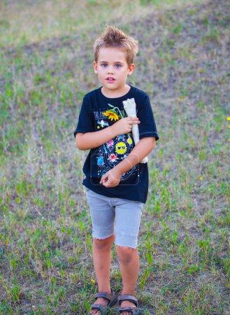 Photo pour Portrait d'un garçon de 5 ans en plein air vérifiant un os d'animal . - image libre de droit