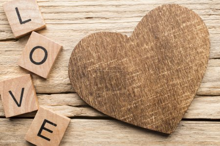 Photo for Wood heart on old wooden background - Stock Image. I love you, cast out of wood kubik. - Royalty Free Image
