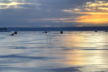 Early morning view of ice fishing huts on Lake Cha...