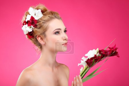 Photo for Beautiful girl, isolated on a pink background with varicoloured flowers in hairs, emotions, cosmetics - Royalty Free Image