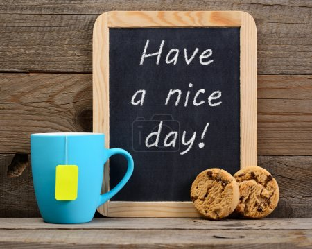 Cup of tea and small blackboard with Have a nice day! phrase