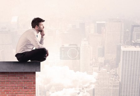 Photo for An elegant businessman in modern suit sitting on the top of a brick building, looking over the cityscape with clouds concept - Royalty Free Image