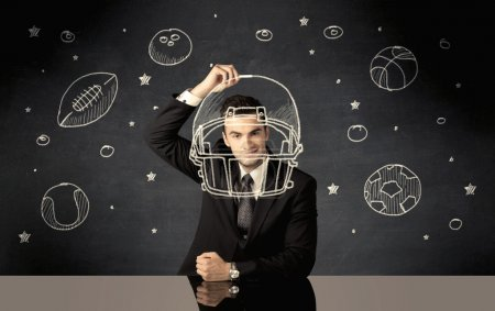 Businessman drawing helmet and sport balls