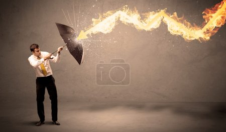 Business man defending himself from a fire arrow with an umbrell