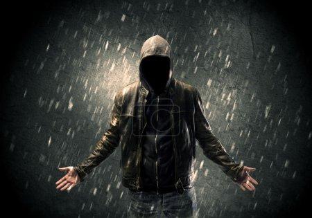 Photo pour Un homme misérable sans visage en sweat à capuche et veste en cuir debout dans l'obscurité avec un concept de silhouette visible - image libre de droit