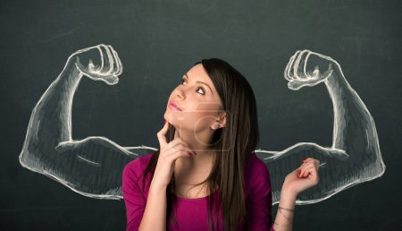 Photo for Pretty young woman with sketched strong and muscled arms - Royalty Free Image