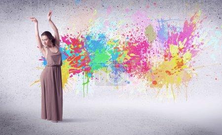 Photo pour Danseuse de rue moderne sautant avec des éclaboussures de peinture colorée sur le concept de mur arrière - image libre de droit