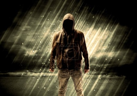 Photo for An incognito hooded stalker standing in the rain with his back in front of dark scary landscape concept - Royalty Free Image