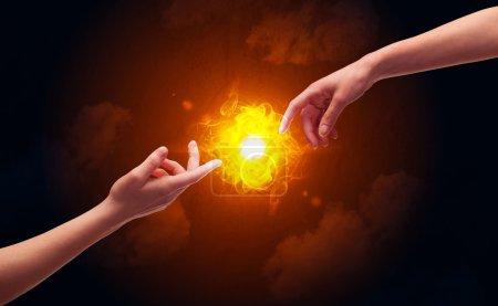 Photo pour Deux mains masculines nues sur le point de toucher, allumant une flamme brillante avec de la fumée dans le ciel rouge concept de fond - image libre de droit
