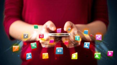 Photo pour Homme tenant smartphone avec des icônes d'application de la technologie sortant - image libre de droit