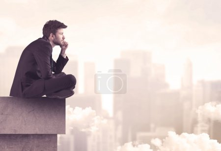 Photo for A serious business person sitting with laptop and tablet at the edge of a tall building, looking over cloudy city scape concept - Royalty Free Image
