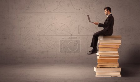 Photo for A serious businessman with tablet in hand in suit sitting on a pile of giant books in front of a greyish brown wall including drawn lines, angles, numbers, circles and curves. - Royalty Free Image
