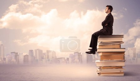 Photo for A serious businessman in elegant suit sitting on a stack of books in front of city scape and clouds - Royalty Free Image