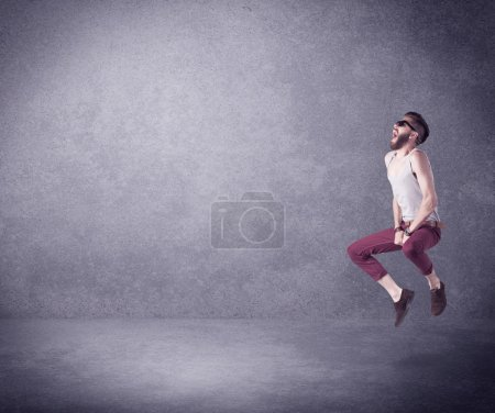 Photo for A hipster guy in stylish clothes shouting in front of an empty urban concrete wall background concept - Royalty Free Image