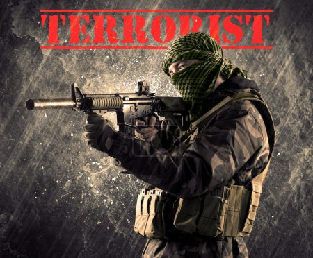 Dangerous masked and armed man with terrorist sign on grungy bac