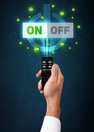 Photo pour Main tenant une télécommande, signal marche / arrêt sortant de i - image libre de droit