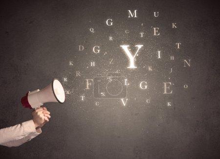 Photo pour Bras caucasien tenant mégaphone avec nuage de lettre - image libre de droit