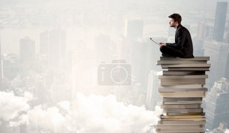 Photo for A serious businessman with laptop tablet in elegant suit sitting on a stack of books in front of cityscape - Royalty Free Image