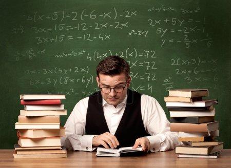 Photo pour Un jeune professeur ambitieux en lunettes assis au bureau de classe avec une pile de livres devant le tableau noir plein de calculs mathématiques, de chiffres, de concept de retour à l'école . - image libre de droit