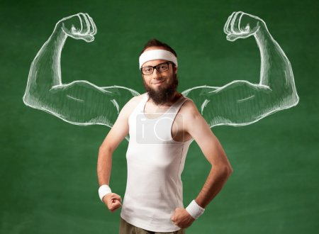 Photo for A young male with beard and glasses posing in front of green background, imagining how he would look like with big muscles, illustrated by white drawing concept. - Royalty Free Image