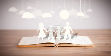 Photo for Cardboard figures of the family on opened book. The symbol of unity and happiness - Royalty Free Image