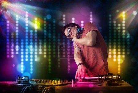 Photo pour Jeune dj jouant des chansons dans une discothèque avec spectacle de lumière - image libre de droit