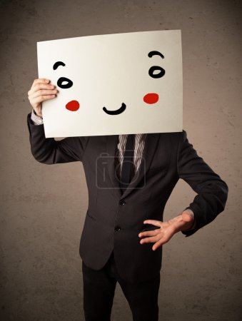 Photo for Young businessman holding a cardboard with a smiley face on it in front of his head - Royalty Free Image