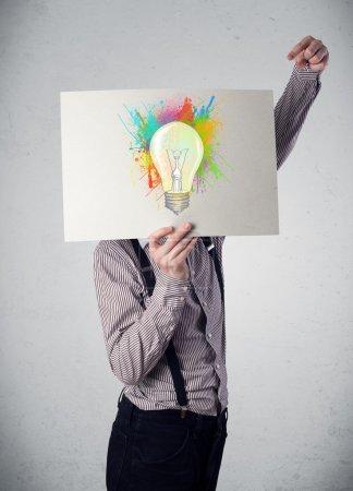 Foto de Empresario sosteniendo un cartón con salpicaduras de pintura de colores y bombilla delante de su cabeza - Imagen libre de derechos
