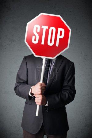 Photo pour Homme d'affaires debout et tenant un panneau stop devant sa tête - image libre de droit