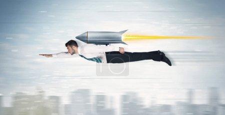 Foto de Hombre de negocios de superhéroe volando con el cohete de jet pack sobre el concepto de ciudad - Imagen libre de derechos