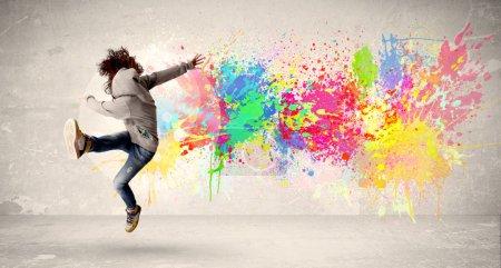 Photo pour Heureux adolescent sautant avec éclaboussure d'encre colorée sur le concept de fond urbain - image libre de droit