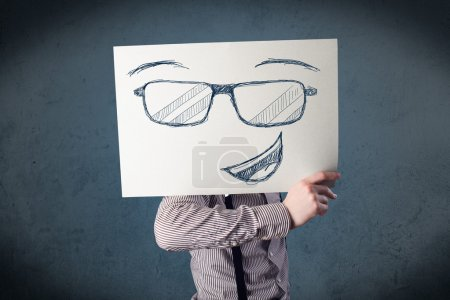Photo for Young businessman holding a paper with smiley face in front of his head - Royalty Free Image