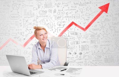Photo pour Femme d'affaires assise à table avec des diagrammes dessinés à la main du marché - image libre de droit