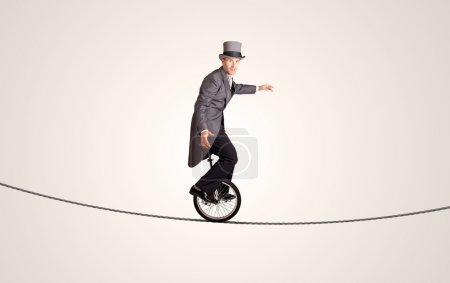 Extreme business man riding unicycle on a rope