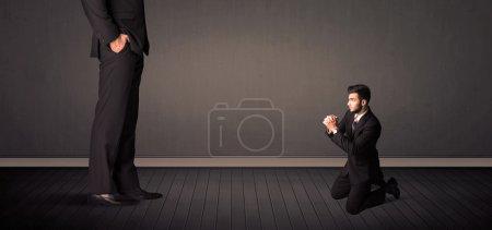 Little bussinesman in front of a giant boss legs c...
