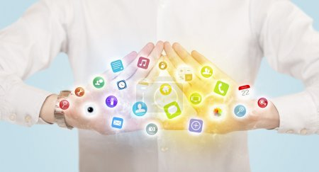 Photo for Hands creating a form with colorful mobile app icons in the cente - Royalty Free Image