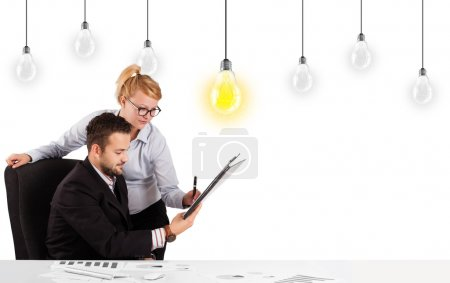 Photo for Business man and woman sitting at table with bright idea light bulbs - Royalty Free Image