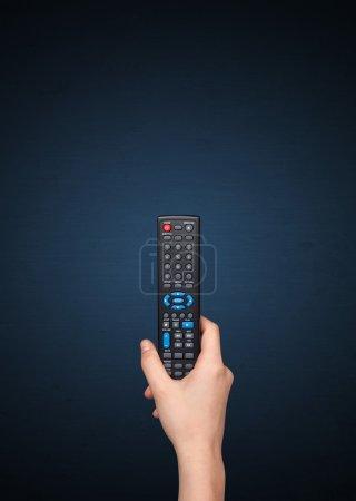 Photo pour Main tenant une télécommande sur fond bleu - image libre de droit