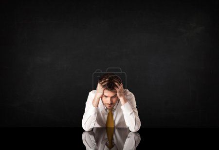 Photo for Depressed businessman sitting at a desk - Royalty Free Image